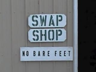 The white sign at the front door of the shop. In green it reads: Swap Shop, No Bare Feet.